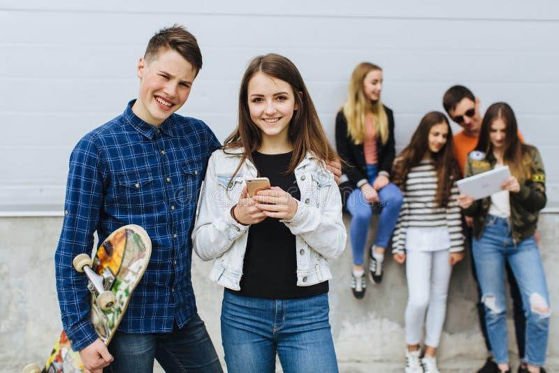 小组有智能手机滑板的微笑的少年 免版税库存图片