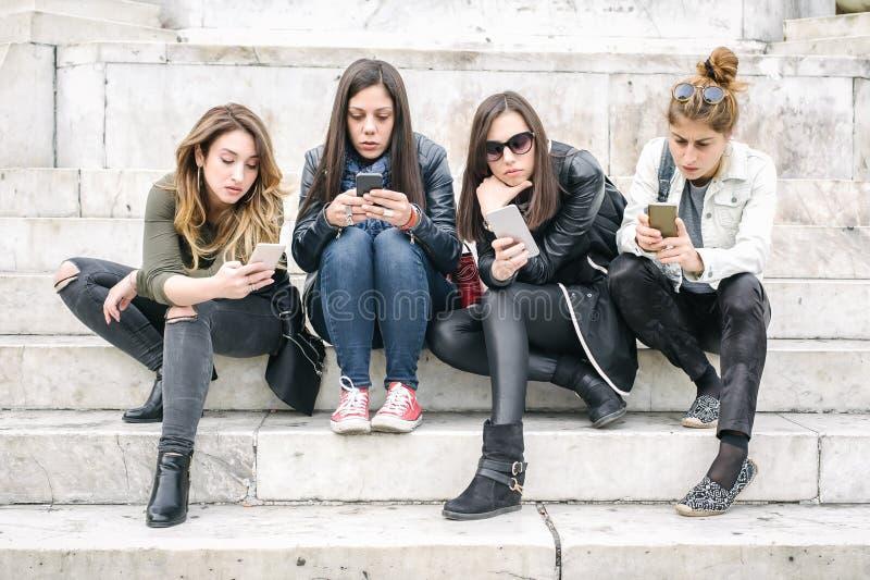 小组有智能手机的女孩 技术隔离和emotio 免版税库存图片