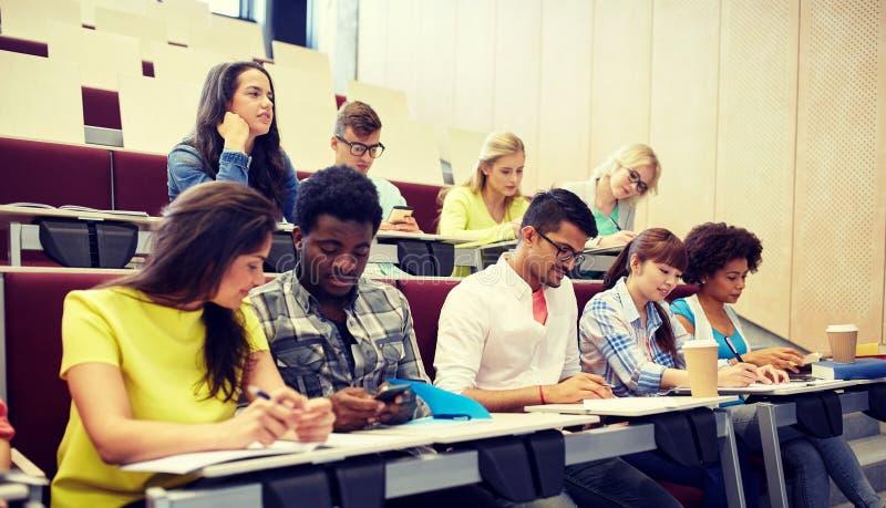 小组有智能手机的学生在演讲 库存图片