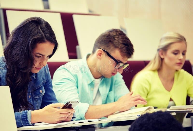小组有智能手机的学生在演讲 免版税库存照片