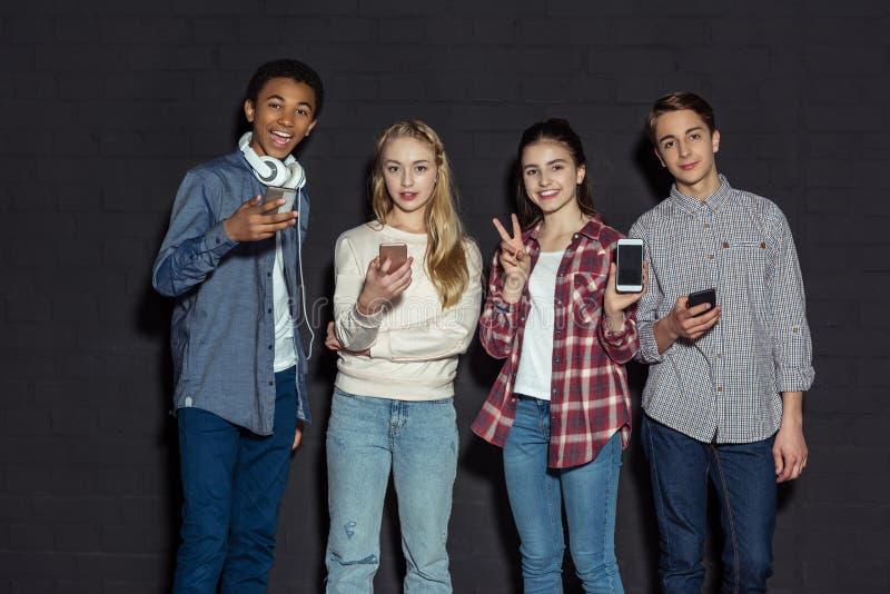 小组有智能手机的时髦的少年 库存图片