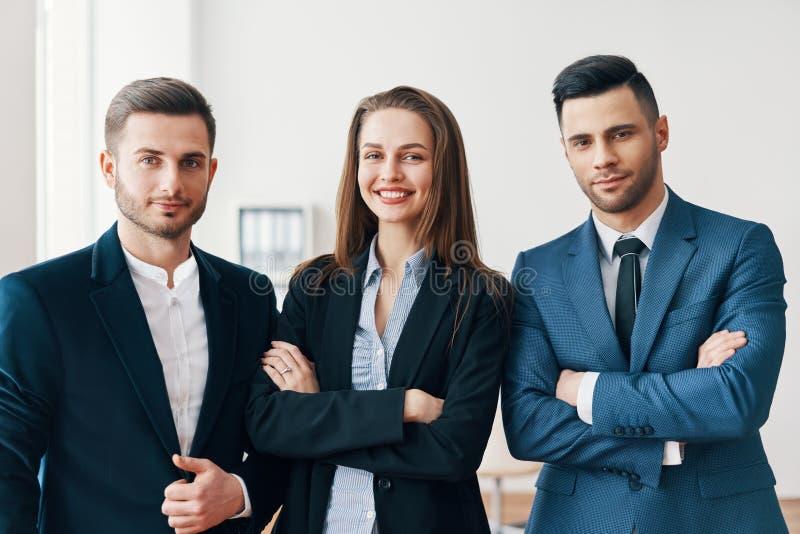小组有有横渡的胳膊的成功的微笑的商人在办公室 免版税库存图片
