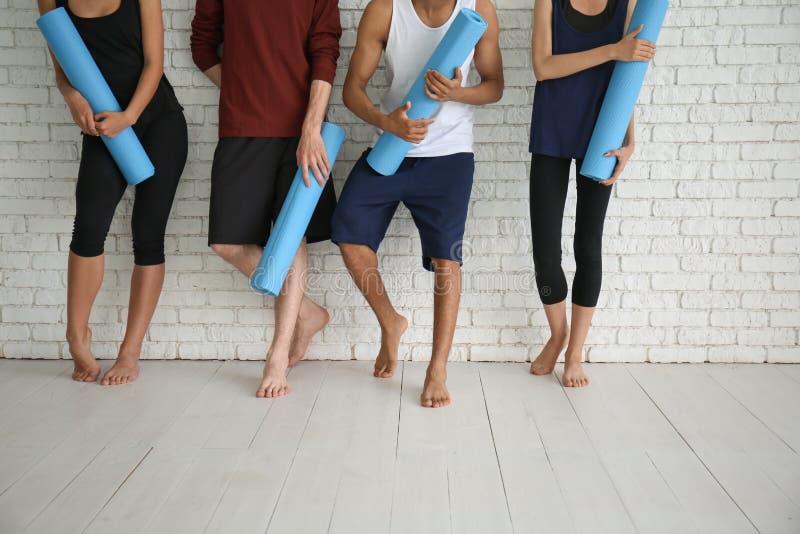 小组有瑜伽席子的运动的人在白色砖墙附近 库存照片
