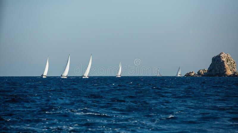 小组有白色风帆的游艇小船在岩石附近在爱琴海 库存照片