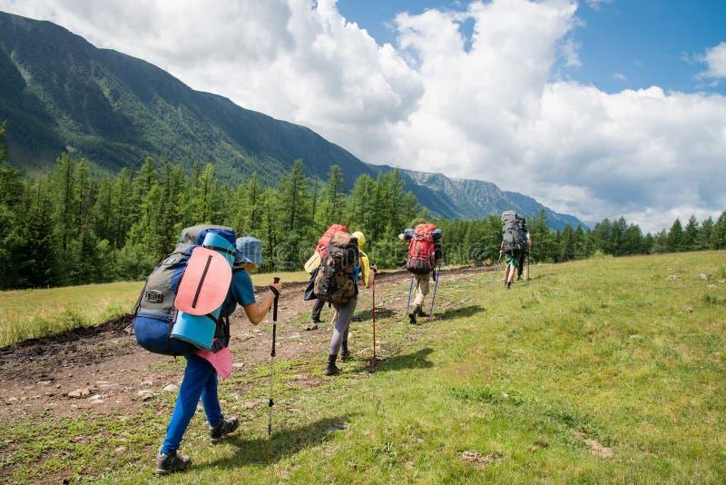 小组有背包的旅客沿往山土坎的一串足迹走在晴天之前 背包徒步旅行者和远足者样式 库存图片