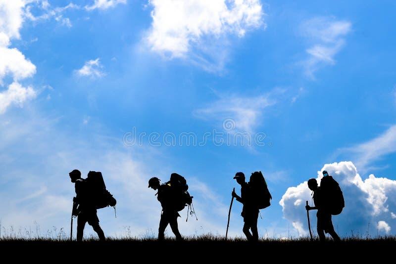小组有背包的旅行家在山顶部 免版税库存照片