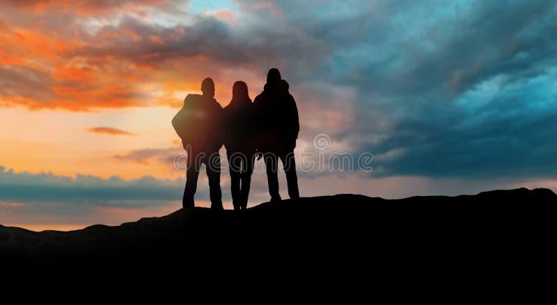 小组有背包的旅行家在日落 免版税库存照片