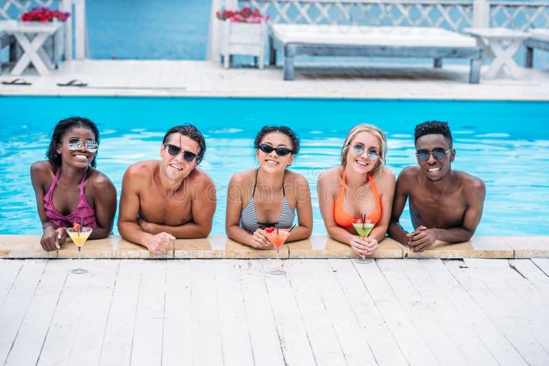 小组有鸡尾酒的年轻愉快的不同种族的人在游泳 免版税库存照片