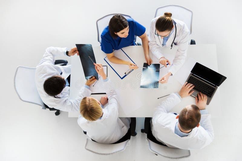 小组有X-射线的在诊所的医生和膝上型计算机 免版税库存图片