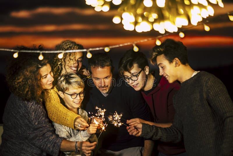 小组朋友一起庆祝圣诞夜或除夕或者生日或者党象周年使用轻的闪闪发光和 免版税图库摄影