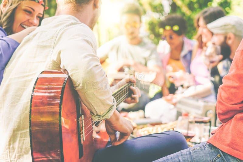 小组朋友有野餐在室外的公园-享受野餐的愉快的年轻伙伴演奏吉他,唱歌的和饮用的酒 库存照片