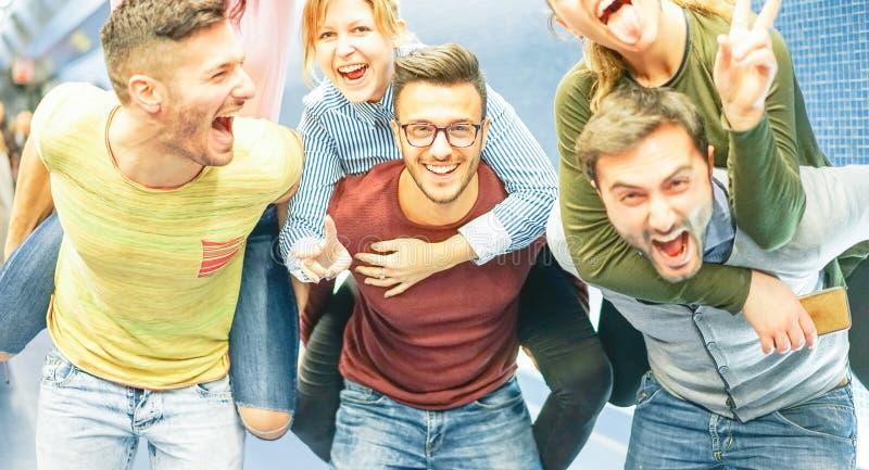 小组朋友获得乐趣在傻事-扛在肩上他们的女朋友的人-做党的年轻人 免版税库存图片