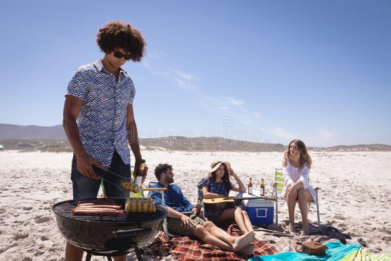 小组朋友获得乐趣在海滩在阳光 免版税库存图片
