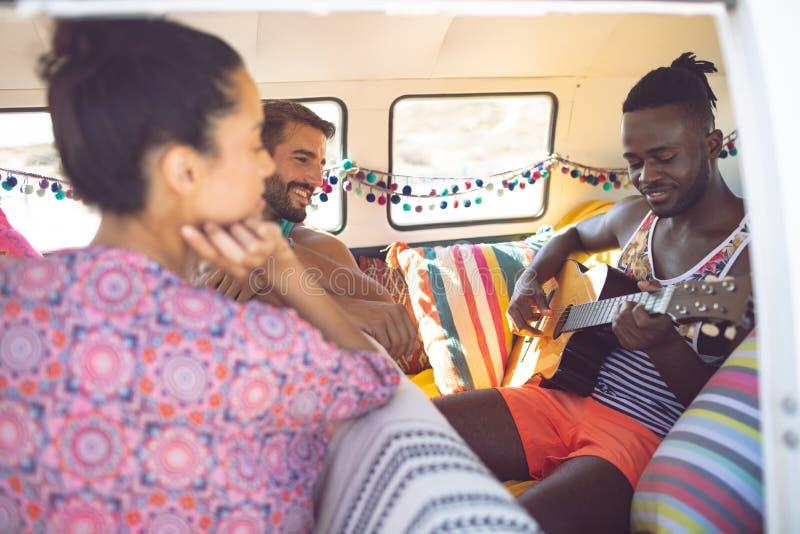 小组朋友获得乐趣在露营者货车在海滩 免版税库存图片