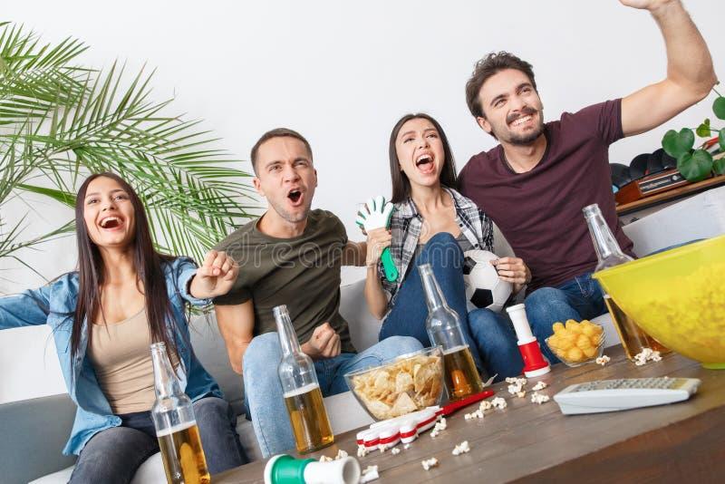 小组朋友观看足球比赛呼喊的体育迷 免版税库存图片