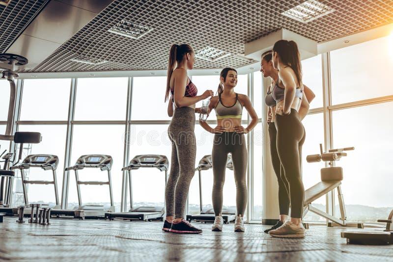 小组朋友谈话在健身俱乐部在坚硬训练天以后 免版税库存图片