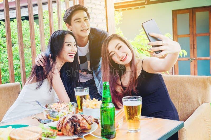 小组朋友采取selfie,并且吃食物是愉快的enj 库存图片
