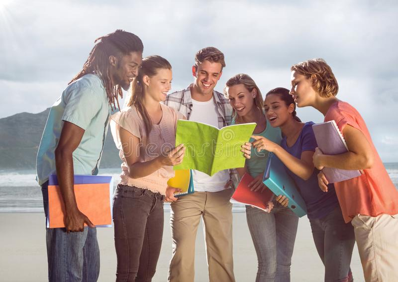 小组海滩的朋友与书 库存图片