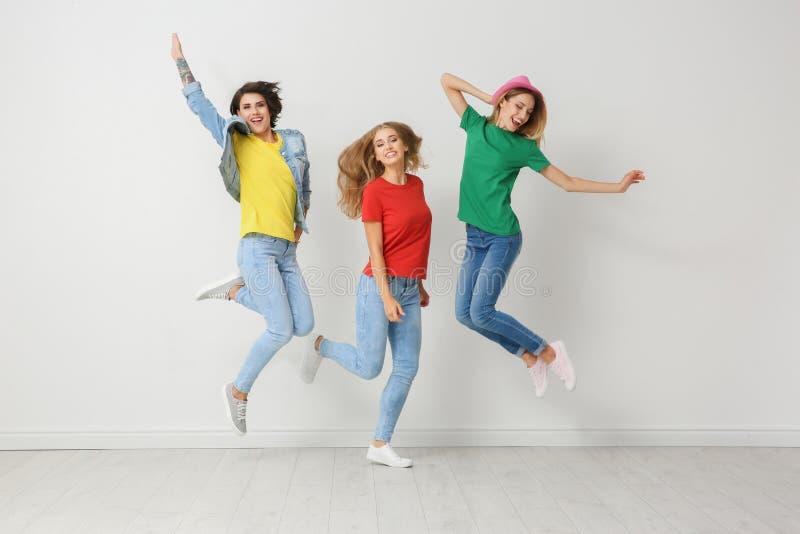 小组牛仔裤和五颜六色的T恤杉的少妇 免版税库存图片