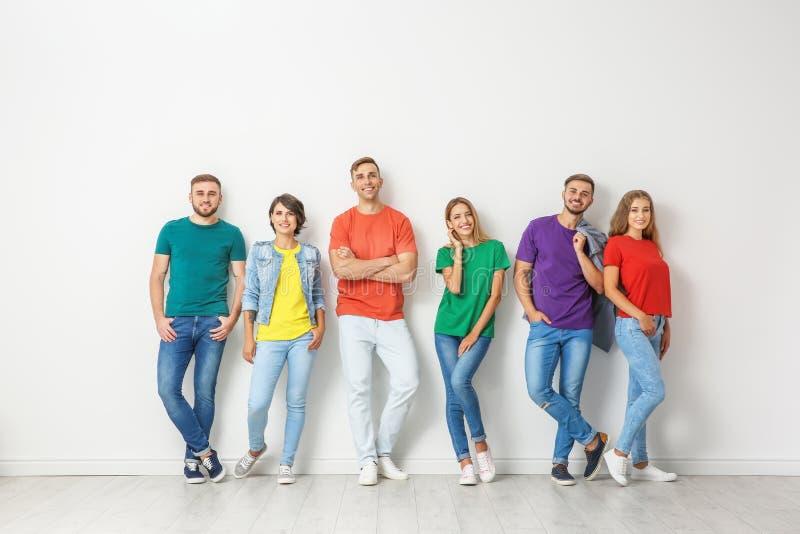 小组牛仔裤和五颜六色的T恤杉的青年人 库存照片