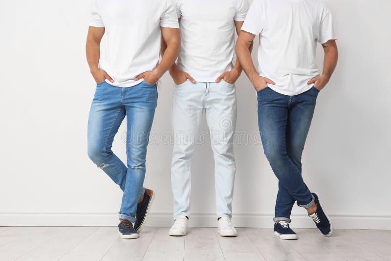 小组牛仔裤的年轻人临近墙壁 免版税库存图片