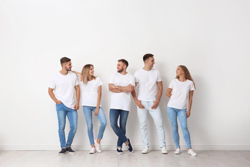 小组牛仔裤的青年人临近墙壁 库存图片