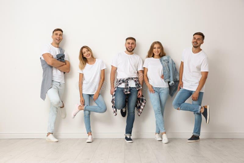 小组牛仔裤的青年人临近墙壁 免版税库存图片
