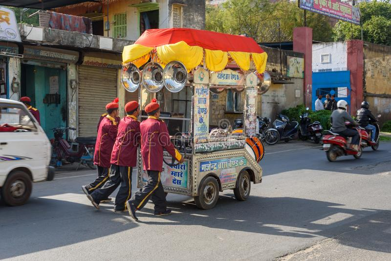 小组男性艺术家在阿杰梅尔推挤在街道上的音乐推车 ?? 库存图片