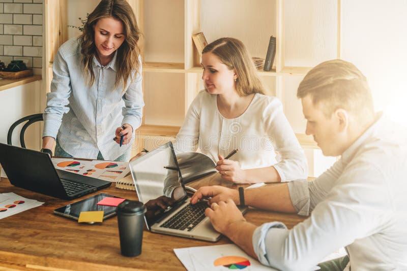 小组的青年人 人使用膝上型计算机,看在膝上型计算机屏幕上的女孩,谈论经营计划 库存图片