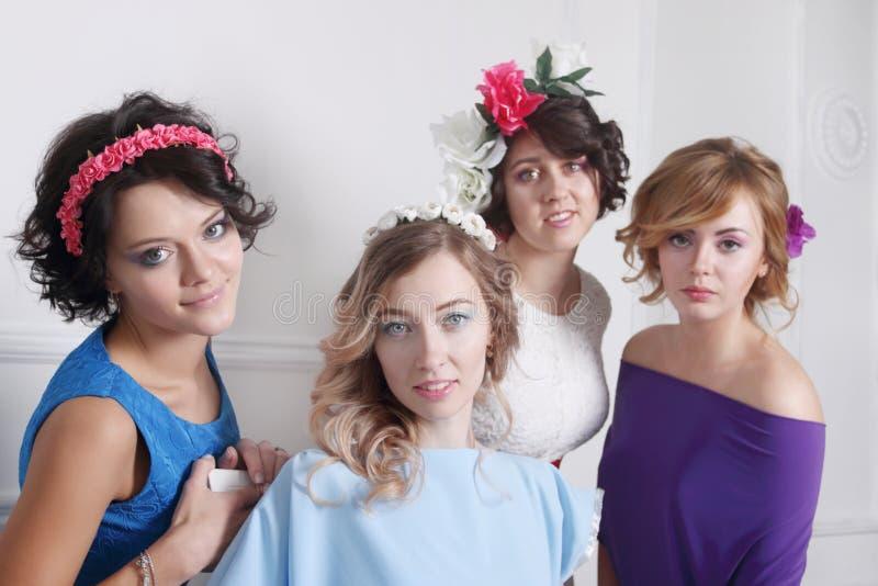 小组礼服的四个美丽的女孩有花的 库存图片