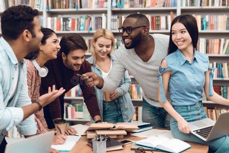 小组种族多文化学生谈论学习在图书馆 免版税库存照片