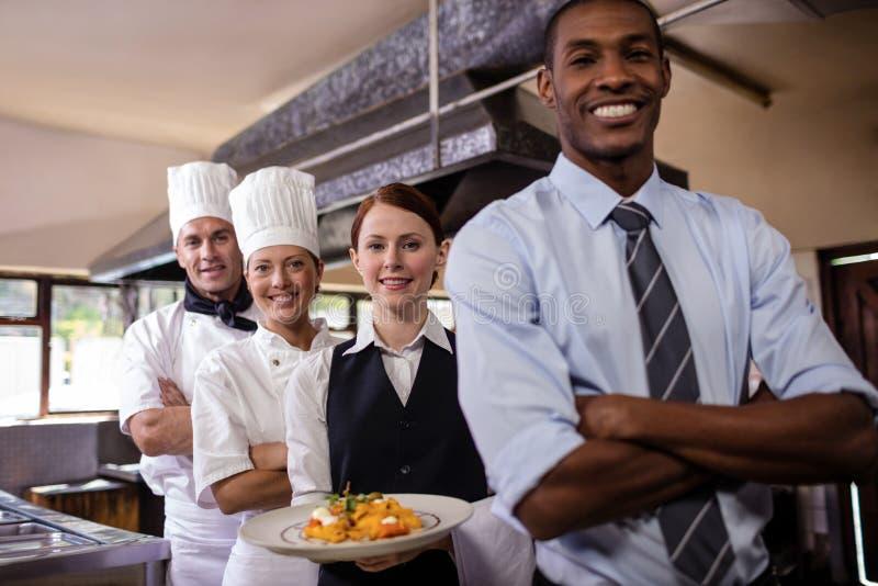 小组站立与armas的旅馆职员横渡在厨房里 免版税库存照片