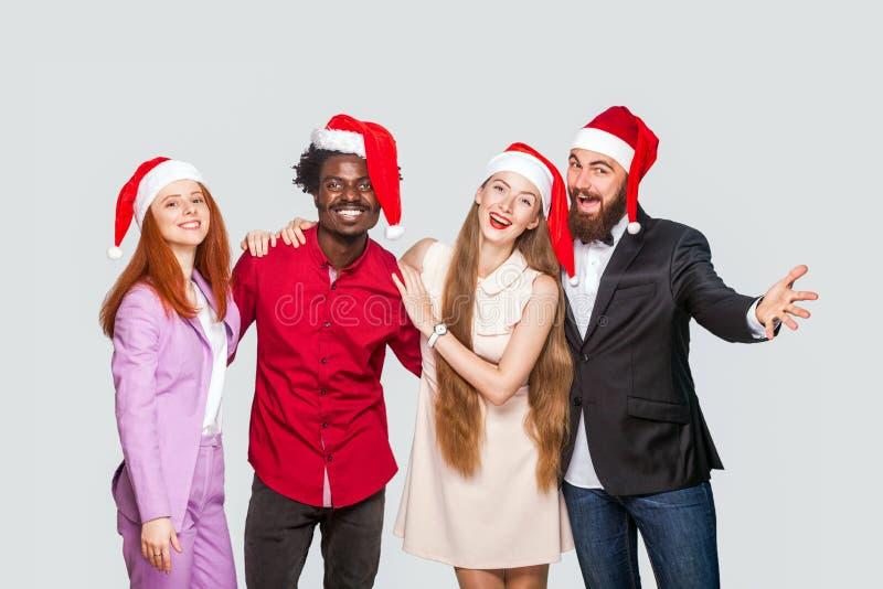 小组站立红色的盖帽的美丽的愉快的英俊的朋友  库存图片
