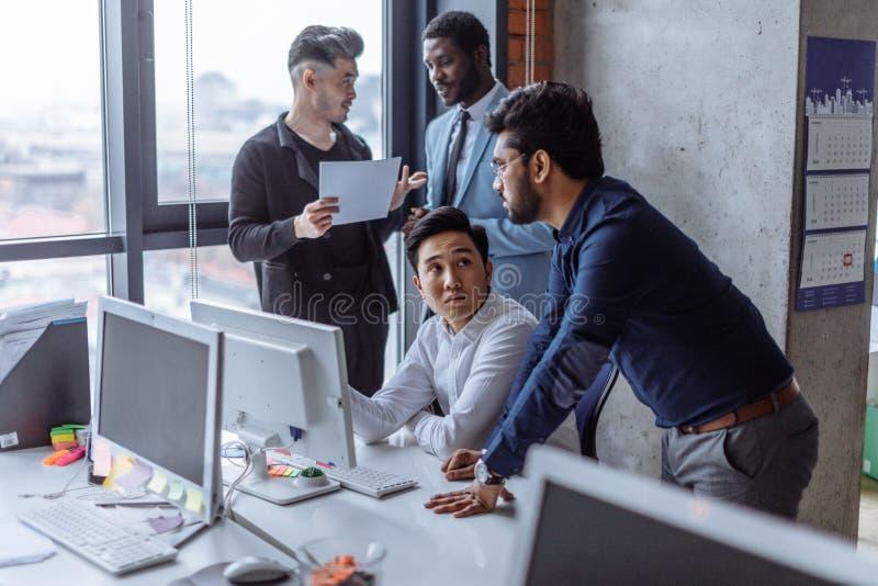小组聚焦了在办公室谈话的桌附近被会集的男性商人 免版税图库摄影