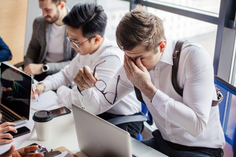 小组聚焦了在办公室谈话的计算机附近被会集的男性商人 库存图片