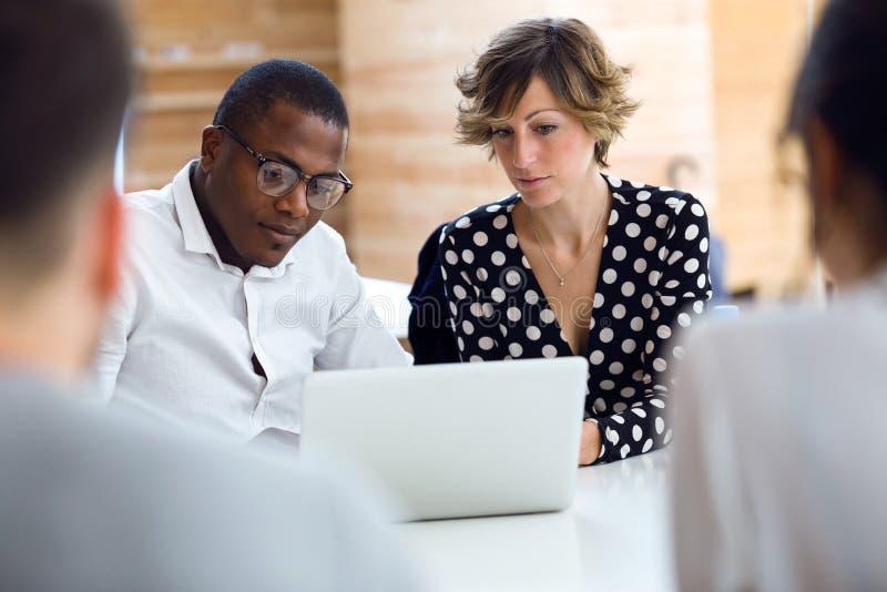 小组聪明的年轻买卖人与在coworking的地方的膝上型计算机一起使用 免版税库存图片