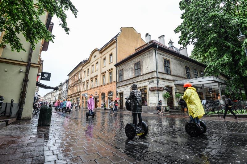 小组自平衡的滑行车的游人在游览在老镇克拉科夫,波兰 Szewska街道建筑学  图库摄影