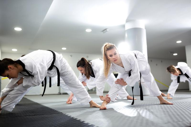 小组舒展和训练与他们的完全残疾朋友一起的跆拳道运动员 免版税库存图片