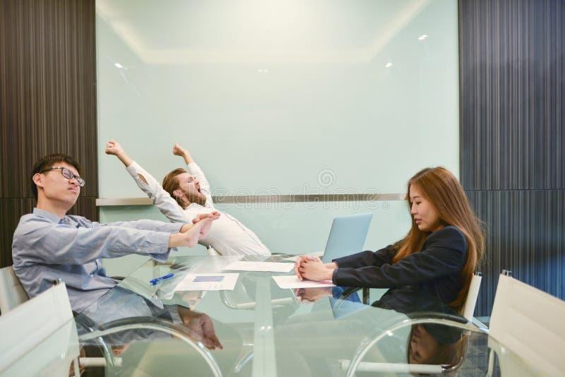 小组舒展在有空白的p的会议室的商人 免版税库存照片
