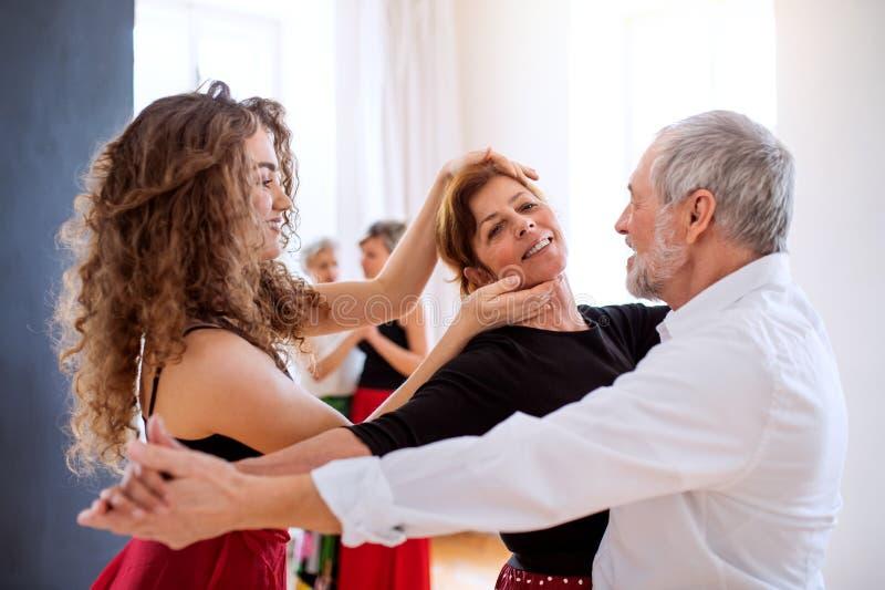 小组舞蹈课的资深人与舞蹈老师 免版税库存图片