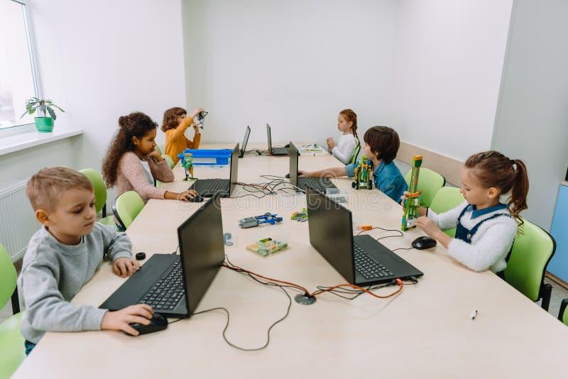 小组被聚焦的孩子与计算机一起使用 库存图片