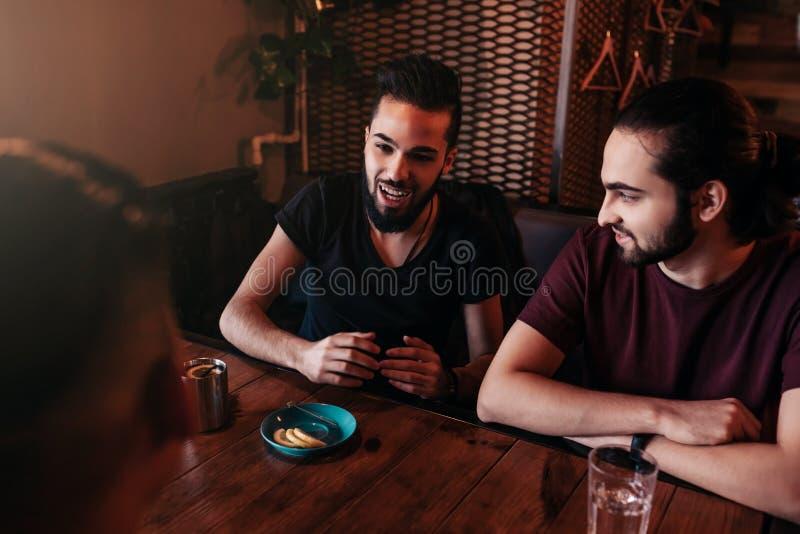 小组谈话和笑在休息室酒吧的混合的族种年轻人 多种族朋友获得乐趣在咖啡馆 人住处 免版税库存照片