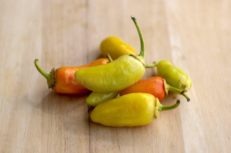 小组辣子墨西哥胡椒numex彩饰陶罐种类、黄色和橘黄色在木桌,墨西哥烹调非常热的成份上 库存图片
