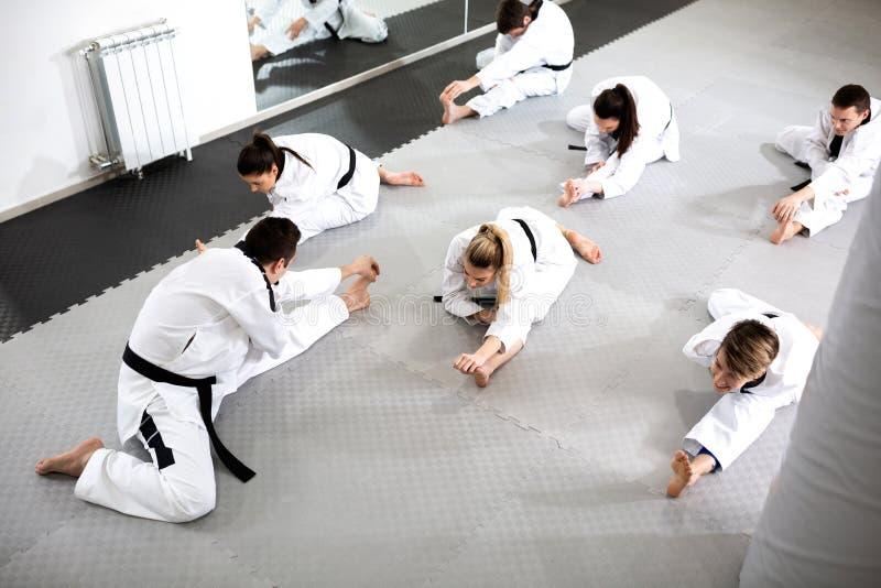 小组运动员伴随于完全挑战运动员为作战训练锻炼做准备 库存图片