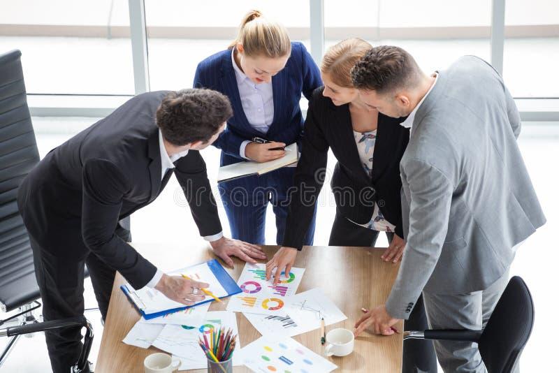 小组遇见会议的商人在办公室 一起群策群力配合的销售的队在工作区 讨论 库存照片