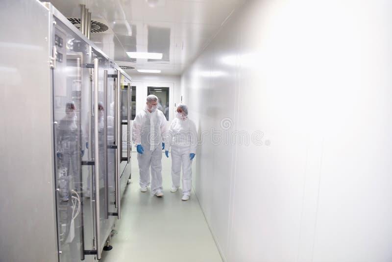 小组防护服装的工作者在f的一间无菌室 免版税库存图片