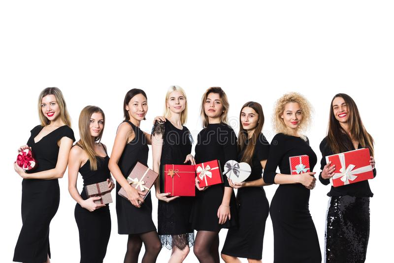 小组黑礼服的时尚妇女有礼物的在被隔绝的手上 库存照片