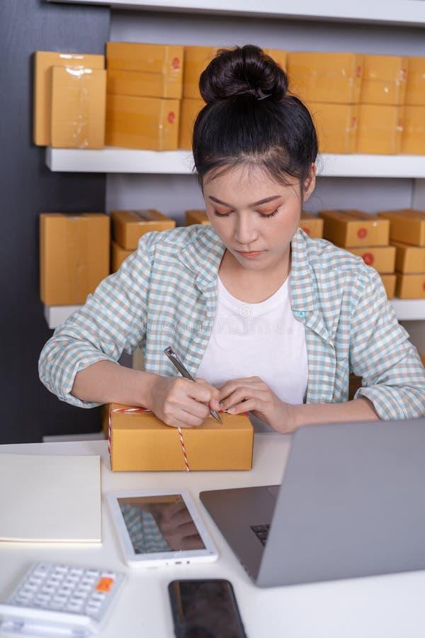 小网上企业主,妇女与膝上型计算机一起使用准备p 库存照片
