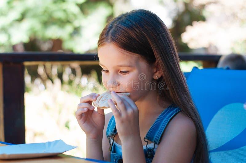 小美丽的女孩吃以胃口在大阳台餐馆夏天 免版税库存图片