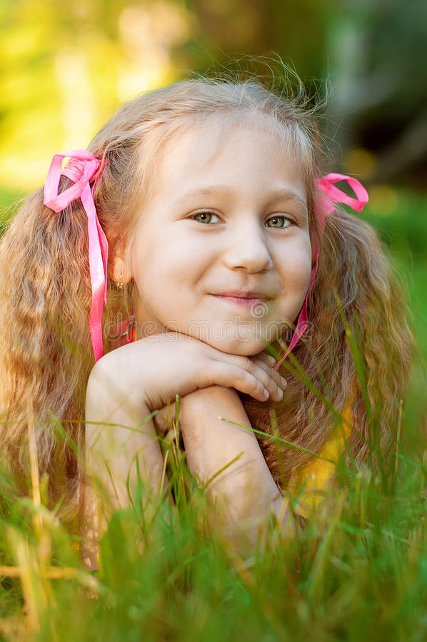 小美丽的女孩在绿草,在城市pa的太阳夏天说谎 图库摄影